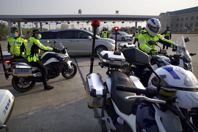 Police officers wearing face masks to protect against the spread of new coronavirus sit on motorcycles near a toll gate for vehicles entering and exiting Wuhan in central China's Hubei Province, Wednesday, April 8, 2020. After 11 weeks of lockdown, the first train departed Wednesday morning from a re-opened Wuhan, the origin point for the coronavirus pandemic, as residents once again were allowed to travel in and out of the sprawling central Chinese city. (AP Photo/Ng Han Guan)