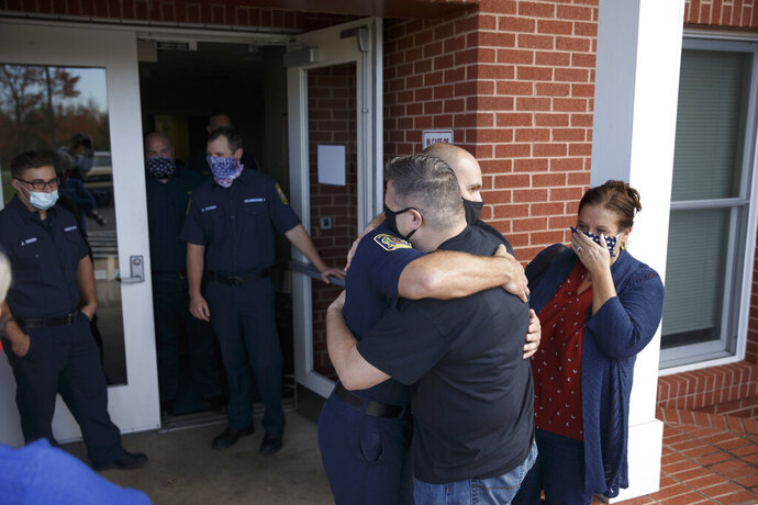 Billie Demarest gets a hug from emergency technician Nathan Ogden as he meets the fire and rescue personnel who saved his life after he suffered a massive heart attack in Spotsylvania, Va.   Rescue personnel credited Billie's survival in part to her quick application of CPR. (Mike Morones/The Free Lance-Star via AP)