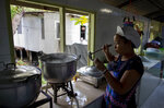 Katsane Sattapitak tastes a meal she is cooking for school children at Makkasan preschool kitchen in Bangkok, Thailand, Wednesday, June 24, 2020. During the third month that schools remained closed due to the coronavirus outbreak,  teachers have cooked meals, assembled food parcels and distributed them to families in this community sandwiched between an old railway line and a khlong, one of Bangkok's urban canals. (AP Photo/Gemunu Amarasinghe)