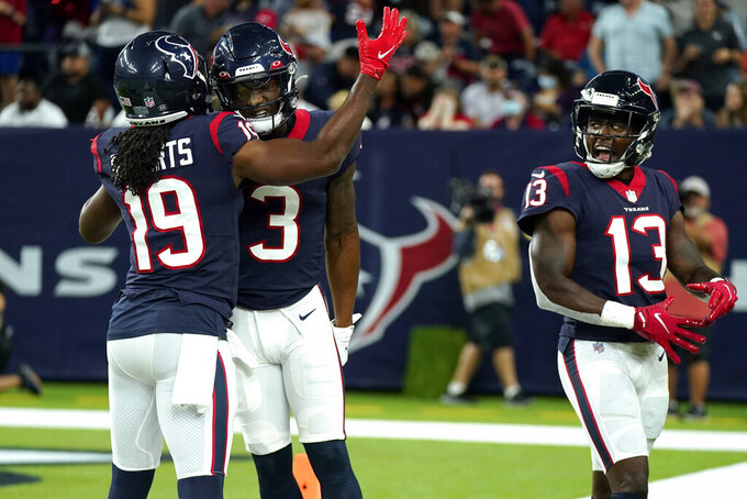 Houston Texans' Anthony Miller (3) celebrates with Andre Roberts (19) and Brandin Cooks (13) after making a touchdown catch against the Carolina Panthers during the first half of an NFL football game Thursday, Sept. 23, 2021, in Houston. (AP Photo/Eric Christian Smith)