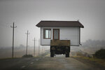 A family drives a truck loaded with a small house along a highway as they leave their home village in the separatist region of Nagorno-Karabakh on Nov. 18, 2020, before a cease-fire takes effect to halt weeks of fighting. Under the Russia-brokered agreement, Armenia will turn over control of some areas it holds outside the separatist territory's borders to Azerbaijan, and Armenians there will be forced to leave their homes. (AP Photo/Sergei Grits)
