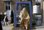 FILE - In this Monday, Sept. 14, 2020 file photo, students walk through a disinfectant tunnel as they arrive to Benazir Bhutto Women University for an examination ahead the university reopening in Peshawar, Pakistan. As coronavirus vaccines trickle into some of the poorest countries in Asia, Africa and the Middle East, data suggest some women are consistently missing out, in another illustration of how the doses are being unevenly distributed around the world. (AP Photo/Muhammad Sajjad, file)