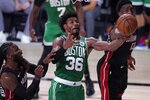 Boston Celtics guard Marcus Smart (36) competes for a rebound against Miami Heat's Jae Crowder, left, and Bam Adebayo, right, during the second half of an NBA conference final playoff basketball game, Saturday, Sept. 19, 2020, in Lake Buena Vista, Fla. (AP Photo/Mark J. Terrill)
