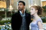 """This image released by Netflix shows Phoebe Dynevor, right, and Rege-Jean Page in a scene from """"Bridgerton."""" The program is nominated for an Emmy Award for outstanding drama series. (Liam Daniel/Netflix via AP)"""