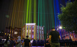 A rainbow light display illuminates the night sky in the West Village neighborhood of New York near The Stonewall Inn, the birthplace of the gay rights movement, on Saturday, June 27, 2020. This year would have been the 50th anniversary of the NYC Pride March, which was canceled because of the coronavirus pandemic. (AP Photo/Bebeto Matthews)