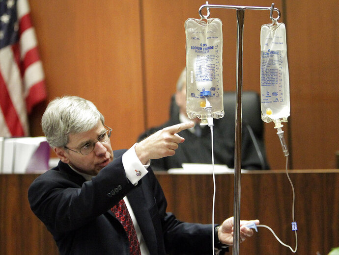 FILE - In this Thursday, Oct. 20, 2011 file photo, anesthesiology expert Dr. Steven Shafer demonstrates the use of propofol after placing a bottle of the drug in an empty saline bag during Dr. Conrad Murray's involuntary manslaughter trial for Michael Jackson's death in Los Angeles. Jackson died 10 years ago at his Los Angeles home after receiving a lethal dose of the drug intended for use only during surgery and other medical procedures _ not for insomnia. (AP Photo/Reed Saxon, Pool)
