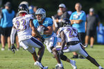 Carolina Panthers running back Christian McCaffrey, center, looks for running room as he carries the football against Baltimore Ravens cornerbacks Anthony Averett (23) and Tavon Young (25) during a joint practice hosted by Carolina at the NFL football team's training camp in Spartanburg, S.C., Wednesday, Aug. 18, 2021. (AP Photo/Nell Redmond)