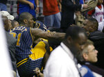 FILE - In this Nov. 19, 2004, file photo, Indiana Pacers forward Ron Artest gets into the stands to fight with some fans during a brawl st an NBA game with the Detroit Pistons, in Auburn Hills, Mich. Violence is part of the game in many sports. But when the Cleveland's Myles Garrett ripped the helmet off Mason Rudolph and hit the Pittsburgh Steelers' quarterback in the head with it, the Browns' defender crossed a line _ one that attracts the attention of authorities sometimes from within their sport and in other cases from criminal prosecutors. (AP Photo/Duane Burleson, File)
