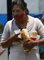 A woman wearing a mask against the spread of the new coronavirus carries a meal that she got from the mobile dining rooms program as people who have not been able to work because of the COVID-19 pandemic line up for a meal outside the Iztapalapa hospital in Mexico City, Wednesday, May 20, 2020. (AP Photo/Marco Ugarte)