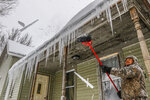 Ha Thao, of Wausau, chips off frozen spikes of ice on top of his front porch Tuesday, Feb. 12, 2019, in Wausau, Wis. The latest snow storm to move through the state dropped several inches of snow overnight. (T'xer Zhon Kha/The Post-Crescent via AP)