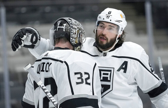 Los Angeles Kings defenseman Drew Doughty (8) hugs goaltender Jonathan Quick (32) after the team's 4-2 victory over the San Jose Sharks in an NHL hockey game Saturday, April 10, 2021, in San Jose, Calif. (AP Photo/Tony Avelar)