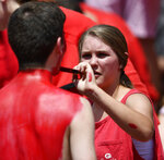 A young woman paints the body of a Georgia fan before the first half of an NCAA college football game between Georgia and Austin Peay, Saturday, Sept. 1, 2018, in Athens, Ga. (AP Photo/Mike Stewart)