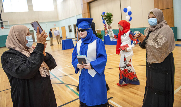 Melak Jashaami, center, is surrounded by family and friends dancing and clapping in a traditional Arabic celebration honoring Jashaami's graduation on Wednesday, Aug. 12, 2020 from Lewiston High School. The single person ceremonies happened at hour intervals through the day at Connors Elementary School in Lewiston to keep participants safer from the risk of COVID-19 transmission.  (Andree Kehn/Sun Journal via AP)