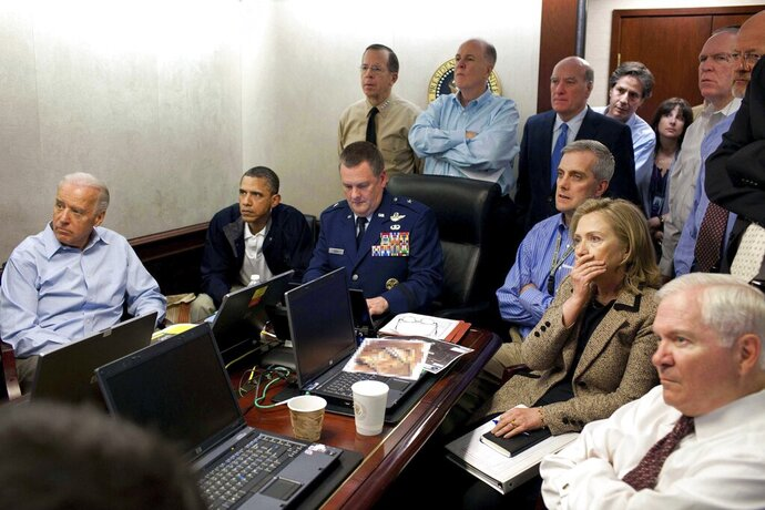 FILE - In this May 1, 2011 image released by the White House and digitally altered by the source to diffuse the paper in front of Secretary of State Hillary Clinton, President Barack Obama and Vice President Joe Biden, along with with members of the national security team, receive an update on the mission against Osama bin Laden in the Situation Room of the White House in Washington. On Friday, Nov. 1, 2019, The Associated Press reported on stories circulating online incorrectly asserting that Biden, while vice president, leaked the identities of special ops SEAL Team 6 who captured Osama bin Laden. On May 3, 2011, Biden gave an address at a Washington-based foreign policy think tank, where he praised the team that killed bin-Laden but he did not mention any of the members by name. (AP Photo/The White House, Pete Souza, File)