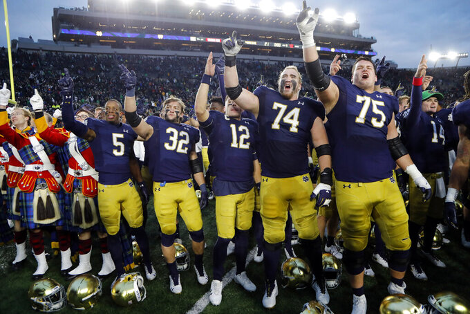 FILE - In this Nov. 2, 2019, file photo, members of the Notre Dame football team sing after an NCAA college football game against Virginia Tech in South Bend, Ind. The Atlantic Coast Conference and Notre Dame are considering whether the Fighting Irish will give up their treasured football independence for the 2020 season play as a member of the league. (AP Photo/Carlos Osorio, File)