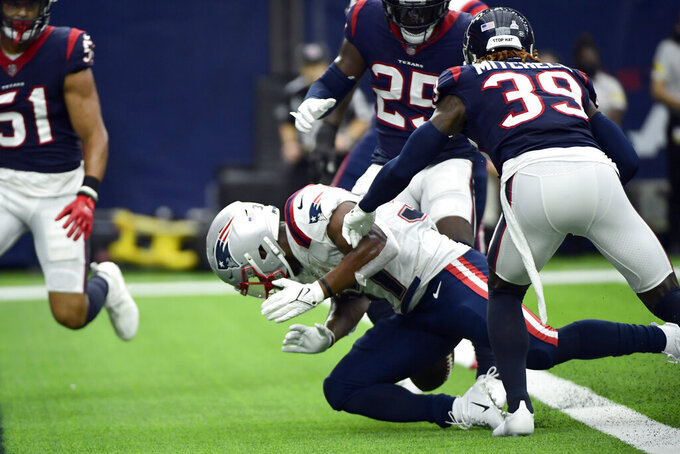 New England Patriots running back Damien Harris, bottom, fumbles the ball at the goal line as he is hit by Houston Texans cornerback Terrance Mitchell (39) during the first half of an NFL football game Sunday, Oct. 10, 2021, in Houston. Houston recovered the fumble. (AP Photo/Justin Rex)