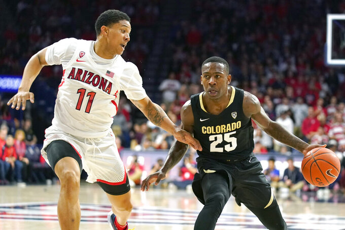 Colorado guard McKinley Wright IV (25) shields the ball from Arizona forward Ira Lee during the first half of an NCAA college basketball game Saturday, Jan. 18, 2020, in Tucson, Ariz. (AP Photo/Rick Scuteri)