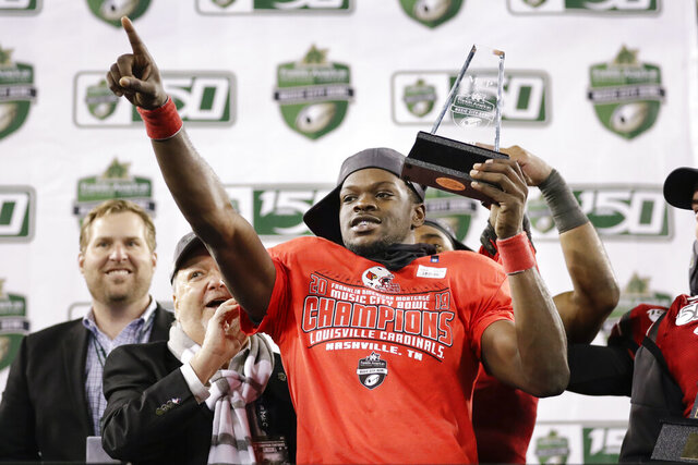 Louisville quarterback Micale Cunningham holds his most valuable player trophy after Louisville beat Mississippi State in the Music City Bowl NCAA college football game Monday, Dec. 30, 2019, in Nashville, Tenn. Louisville won 38-28. (AP Photo/Mark Humphrey)