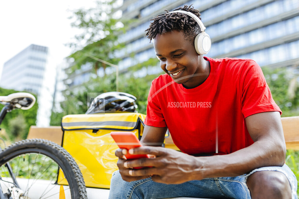 Smiling young delivery man using smartphone while listening music through wireless headphones