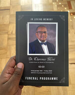 This Wednesday, June 10, 2020 photo provided by Yandi Mini shows him holding the funeral programme of his father,  Dr. Clarence Mini at his Johannesburg home. Clarence Mini, a South African activist and doctor who died of COVID-19 spent his life fighting apartheid, the government's denial of HIV/AIDS and rampant corruption. Loved ones say Mini knew the odds were against him but he was committed to what he believed was right. He died in May at age 69. (Yandi Mini via AP)