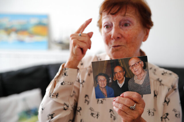 In this photo taken on Friday June 5, 2020, Monette Hayoun displays a photo of her late severely disabled 85-year-old brother, Meyer, center in the picture, flanked with her parents, during an interview in Ivry sur Seine, south of Paris. Families whose elders died behind the closed doors of homes in lockdown are filing wrongful death lawsuits, triggering police investigations. One suit focuses on the death of Meyer Haiun, a severely disabled 85-year-old in a Paris home managed by a Jewish charitable foundation headed Eric de Rothschild, scion of Europe's most famous banking dynasty. (AP Photo/Francois Mori)