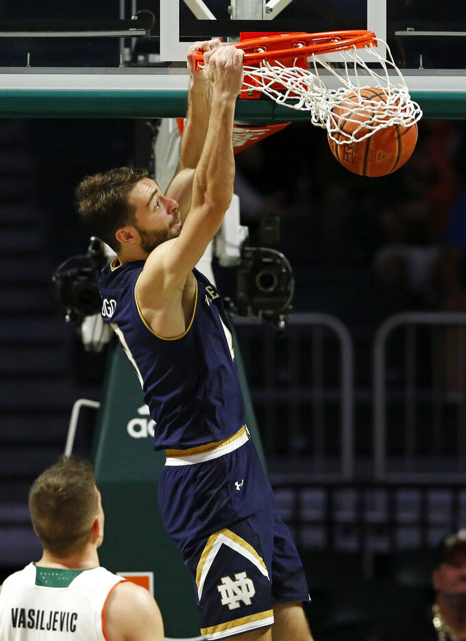 Notre Dame guard Nikola Djogo (13) dunks against Miami guard Dejan Vasiljevic (1) during the second half of an NCAA college basketball game, Wednesday, Feb. 6, 2019 in Coral Gables, Fla. (David Santiago/Miami Herald via AP)