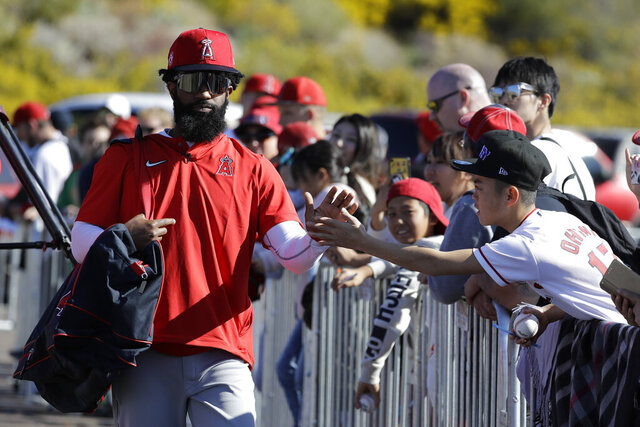 Los Angeles Angels' Brian Goodwin, left, greets a fan during spring training baseball practice, Monday, Feb. 17, 2020, in Tempe, Ariz. (AP Photo/Darron Cummings)