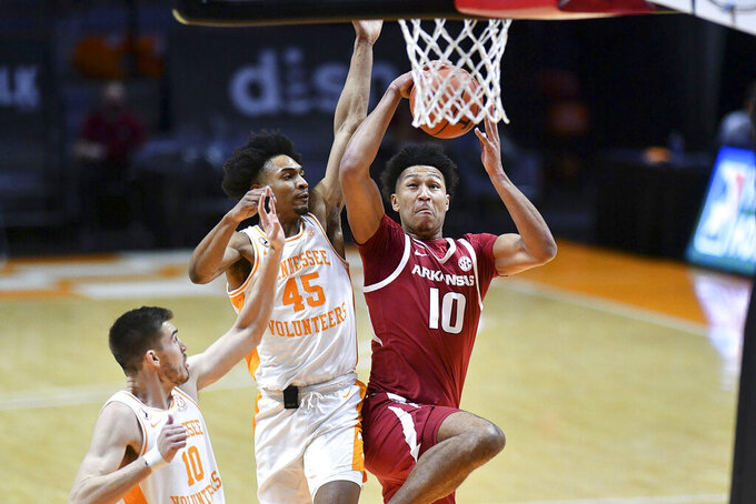 Arkansas' Jaylin Williams (10) attempts to score while guarded by Tennessee's Keon Johnson (45) and John Fulkerson (10) during an NCAA college basketball game Wednesday, Jan. 6, 2021, in Knoxville, Tenn. (Saul Young/Knoxville News Sentinel via AP, Pool)