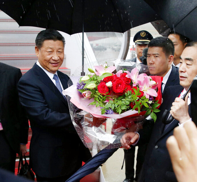 China's President Xi Jinping receives a bunch of flowers on his arrival at Kansai International Airport in Izumisano, Osaka prefecture, western Japan, Thursday, June 27, 2019. Group of 20 leaders gather in Osaka on June 28 and 29 for their annual summit.(Kyodo News via AP)