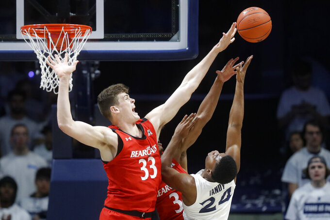 FILE - In this Dec. 7, 2019, file photo, Cincinnati's Chris Vogt (33) blocks a shot by Xavier's KyKy Tandy (24) during the first half of an NCAA college basketball game in Cincinnati. Wisconsin has announced the addition of 7-foot-1 center and Cincinnati transfer Chris Vogt Vogt started 50 games at Cincinnati. He averaged 5 points, 3.5 rebounds and 1.1 blocks and 19.4 minutes last season. (AP Photo/John Minchillo, File)