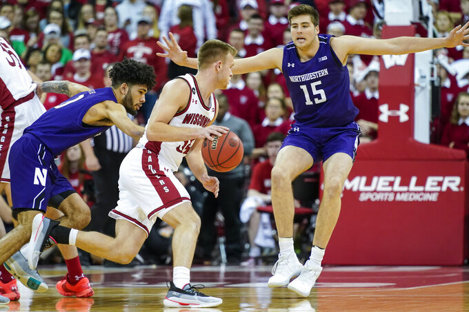Wisconsin's Brad Davison, center, drives between Northwestern's Boo Buie, left, and Ryan Young (15) during the first half of an NCAA college basketball game Wednesday, March 4, 2020, in Madison, Wis. (AP Photo/Andy Manis)