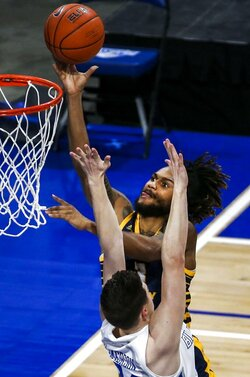 FILE - UMKC guard Brandon McKissic (3) makes a layup over Saint Louis guard Gibson Jimerson (24) during the first half of an NCAA college basketball game in St. Louis, in this Wednesday, Dec. 23, 2020, file photo. Florida added three defensive stalwarts via the NCAA transfer portal, led by two-time Big South defensive player of the year Phlandrous Fleming and Summit League defensive player of the year Brandon McKissic, to bolster a lineup the Gators believe will be able to compete in the stacked Southeastern Conference. (Colter Peterson/St. Louis Post-Dispatch via AP)