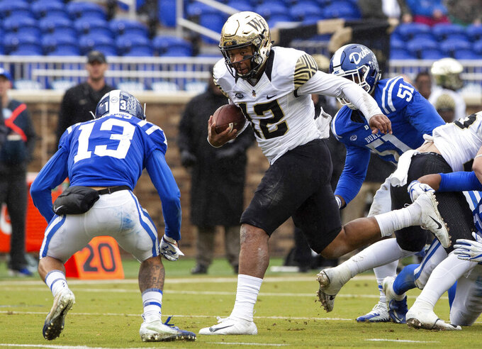 FILE - In this Nov. 24, 2018, file photo, Wake Forest quarterback Jamie Newman (12) carries the ball towards Duke's Jordan Hayes (13) during the first half of an NCAA college football game in Durham, N.C. Newman will begin this season the same way he ended the last one _ as Wake Forest's starting quarterback. Utah State plays at Wake Forest on Friday, Aug. 30. (AP Photo/Ben McKeown, File)