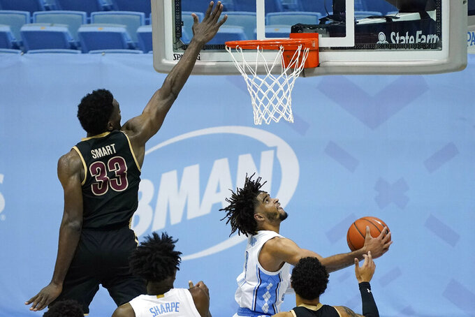 North Carolina guard R.J. Davis drives past College of Charleston center Osinachi Smart (33) during the second half of an NCAA college basketball game in Chapel Hill, N.C., Wednesday, Nov. 25, 2020. (AP Photo/Gerry Broome)