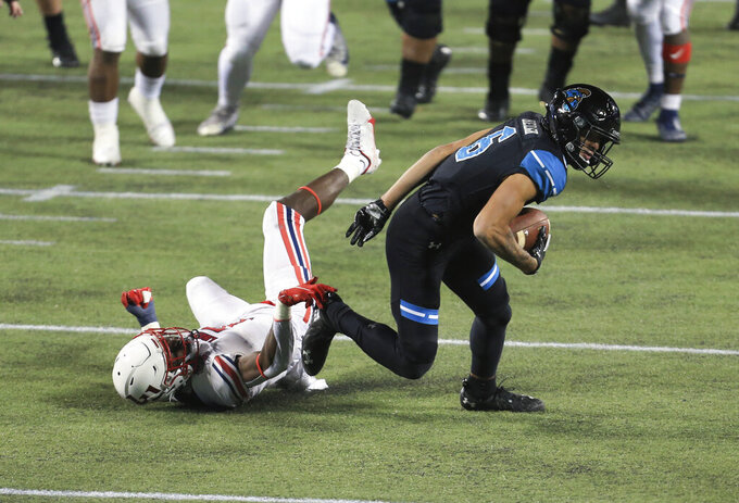 Coastal Carolina wide receiver Jaivon Heiligh (6) escapes the tackle of Liberty safety Marcus Haskins (7) for a first down during the first half of the Cure Bowl NCAA college football game Saturday, Dec. 26, 2020, in Orlando, Fla. (AP Photo/Matt Stamey)