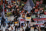 Protesters hold a picture of Philippine President Rodrigo Duterte, center, as they march to protest against the 5th State of the Nation Address of Duterte in Manila, Philippines, Monday, July 27, 2020. (AP Photo/Aaron Favila)