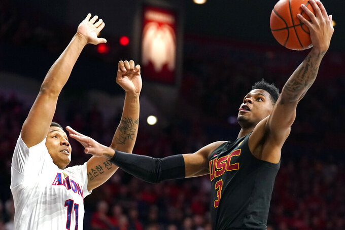 Southern California guard Elijah Weaver (3) shoots as Arizona forward Ira Lee defends during the first half of an NCAA college basketball game Thursday, Feb. 6, 2020, in Tucson, Ariz. (AP Photo/Rick Scuteri)