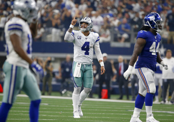 Dallas Cowboys' Dak Prescott (4) celebrates a touchdown as New York Giants linebacker Markus Golden (44) walks away in the first half of a NFL football game in Arlington, Texas, Sunday, Sept. 8, 2019. (AP Photo/Ron Jenkins)