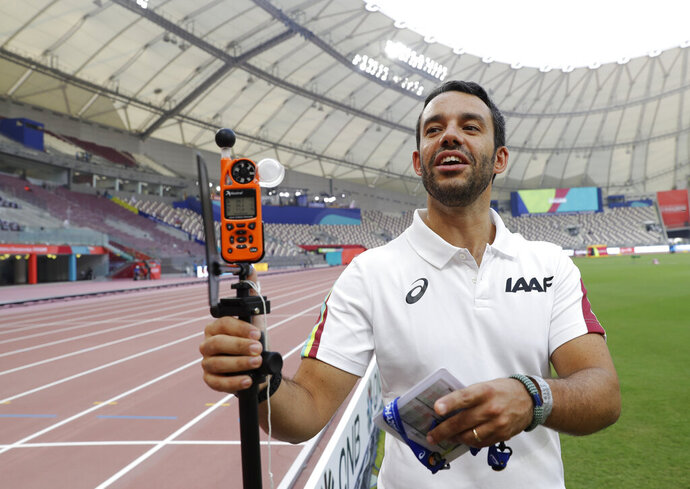 Dr. Paolo Adami explains the use of a heat measuring sensor at the World Athletics Championships in Doha, Qatar, Monday, Sept. 30, 2019. There are around 200 endurance athletes at the world championships swallowing a capsule as part of an IAAF research project on the effects of heat. They couldn't have picked a better time or place in Doha, where the temperatures are soaring. The data could be used to help athletes prepare for the Tokyo Games in less than a year and where conditions are expected to be every bit as stifling. (AP Photo/Petr David Josek)