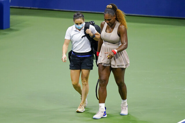 FILE - In this Sept. 10, 2020, file photo, Serena Williams walks to her bench with a trainer for a medical timeout during a semifinal match of the U.S. Open tennis championships, against Victoria Azarenka, of Belarus, in New York. (AP Photo/Seth Wenig, File)