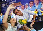 In this Monday, March 18, 2019. a supporter takes a selfie with the leader of Thailand's Democrat Party Abhisit Vejjajiva during an election campaign in Bangkok, Thailand. Abhisit says if he becomes prime minister after Sunday's election, he'll make careful but forceful efforts to undo undemocratic constitutional clauses imposed by the military government that took power in 2014. (AP Photo/Sakchai Lalit)