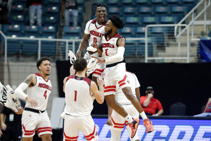 Nicholls State guards Ty Gordon (0) and Kevin Johnson (3) jump to celebrate a 3-point basket by Johnson during the first half of an NCAA college basketball game against Northwestern State in the Southland Conference men's tournament semifinals Friday, March 12, 2021, in Katy, Texas. (AP Photo/Michael Wyke)