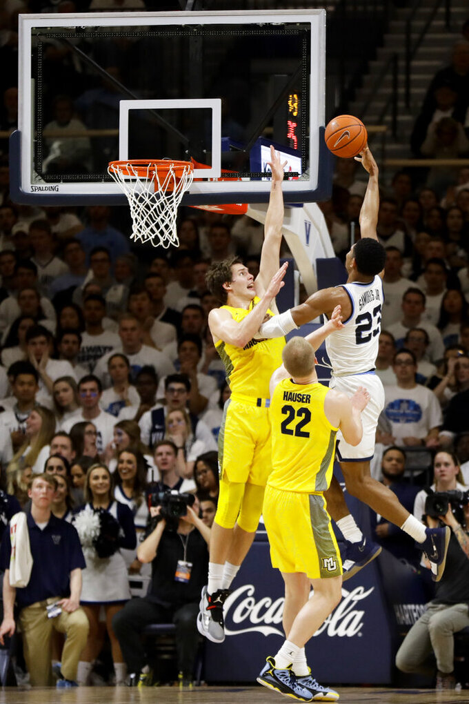 Villanova's Jermaine Samuels, right, goes up for a shot against Marquette's Matt Heldt, left, and Joey Hauser during the first half of an NCAA college basketball game, Wednesday, Feb. 27, 2019, in Villanova, Pa. (AP Photo/Matt Slocum)