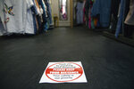 A social distancing sign for customers in a Pop Up Clothing Company store, in Stratford-upon-Avon, Warwickshire, England, Sunday, June 14, 2020. Lockdown restrictions are slowly being eased, which should see the economy start to pick up. On Monday, nonessential shops, such as department stores and electronic retailers, can reopen if they can abide by social distancing requirements. (Jacob King/PA via AP)