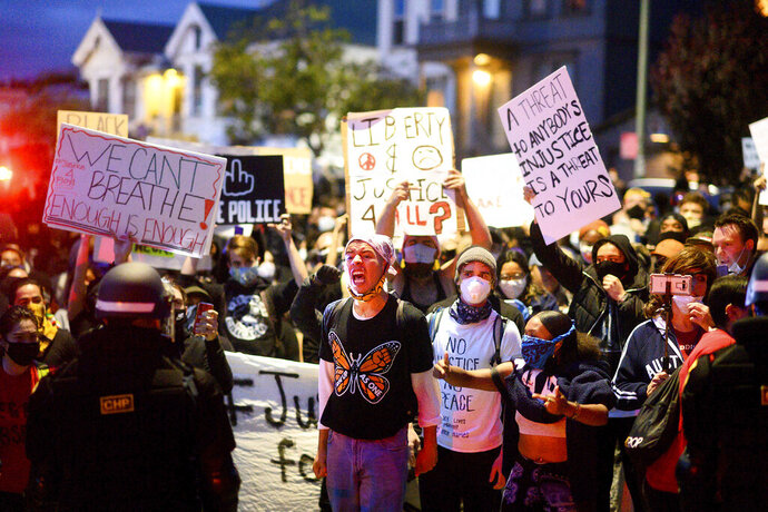 In this May 29, 2020, photo, demonstrators face off against police officers in Oakland, Calif. while protesting the Monday death of George Floyd, a handcuffed black man in police custody in Minneapolis. (AP Photo/Noah Berger)