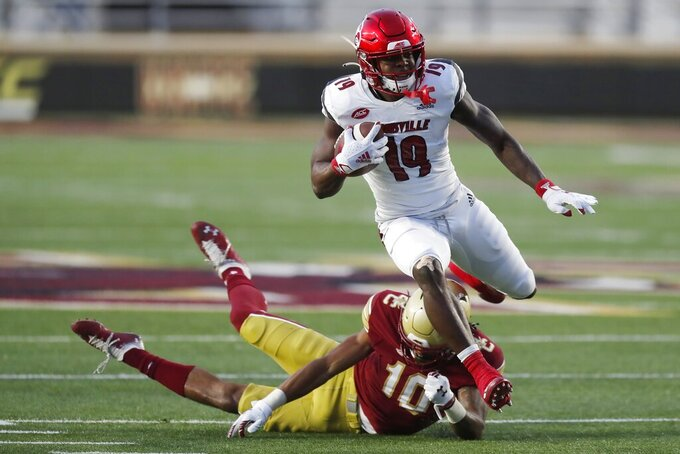 Louisville running back Hassan Hall (19) evades Boston College defensive back Brandon Sebastian (10) during the first half of an NCAA college football game, Saturday, Nov. 28, 2020, in Boston. (AP Photo/Michael Dwyer)