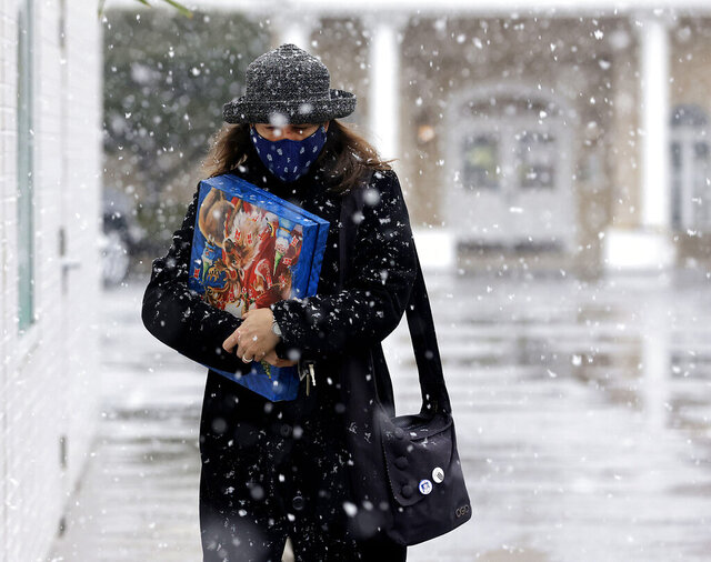 Denise Dutton walks in the snow while shopping on Brookside Wednesday, Dec. 30, 2020, in Tulsa, Okla. (Mike Simons/Tulsa World via AP)