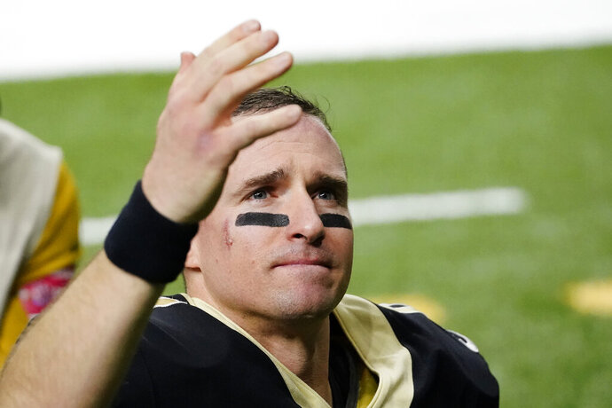 New Orleans Saints quarterback Drew Brees waves to his family and fans after an NFL divisional round playoff football game against the Tampa Bay Buccaneers, Sunday, Jan. 17, 2021, in New Orleans. The Buccaneers won 30-20. (AP Photo/Brynn Anderson)