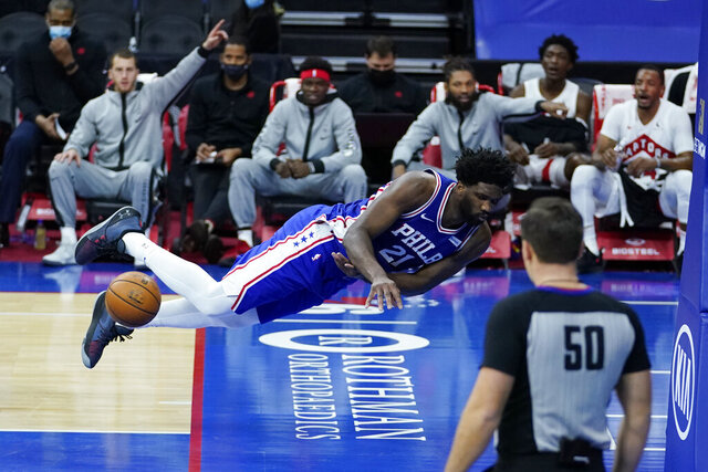 Philadelphia 76ers' Joel Embiid dives to save a loose ball during the first half of an NBA basketball game against the Toronto Raptors, Tuesday, Dec. 29, 2020, in Philadelphia. (AP Photo/Matt Slocum)