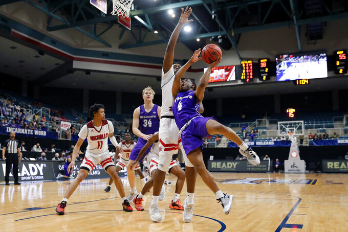 Abilene Christian guard Damien Daniels (4) shoots next to Nicholls State center Ryghe Lyons during the second half of an NCAA college basketball game for the Southland Conference men's tournament championship Saturday, March 13, 2021, in Katy, Texas. (AP Photo/Michael Wyke)